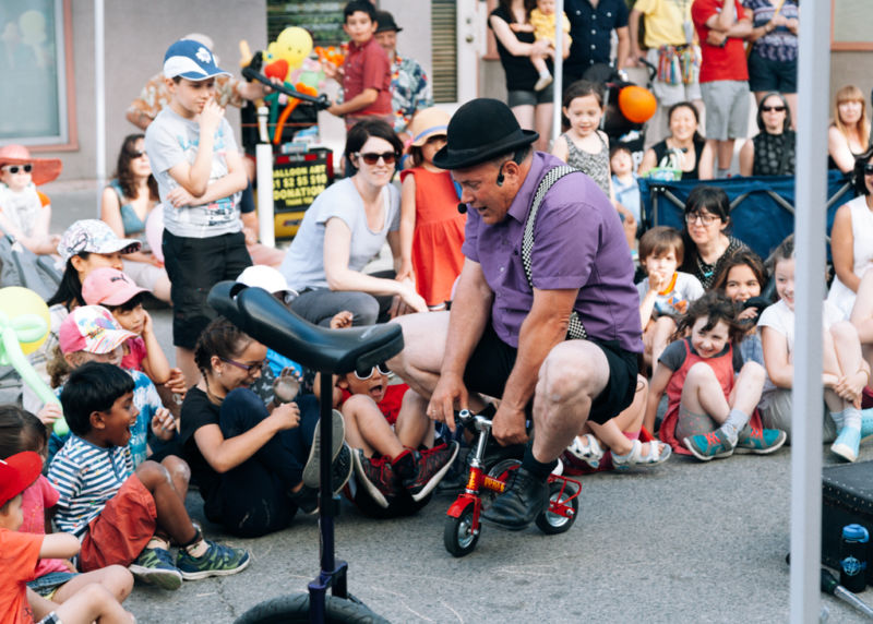 Darren Bedford charms the crowd in the Snug as a Bug Kids Zone at the 2017 Junction Summer Solstice Festival. Busker performances continue to be a Summer Solstice tradition in The Junction. Photo Credit: Yuula Benivolski, 2017