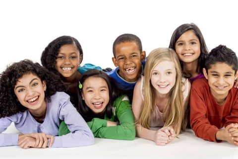 A multi-ethnic group of elementary age children are lying in a row and are smiling and looking at the camera.
